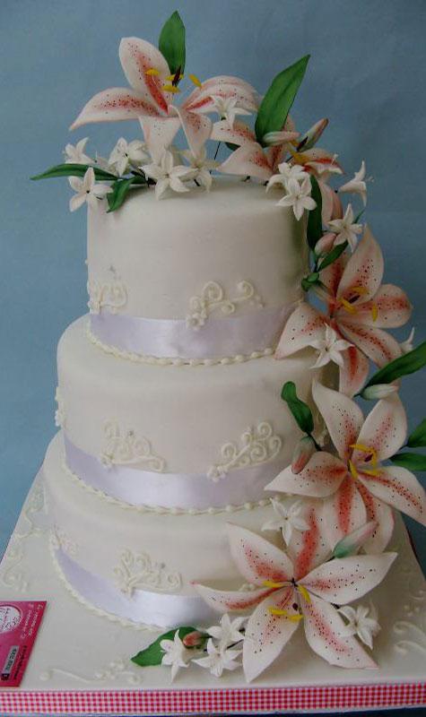 עוגת חתונה בקומות עם עיצובי פרחים מבצק סוכר
